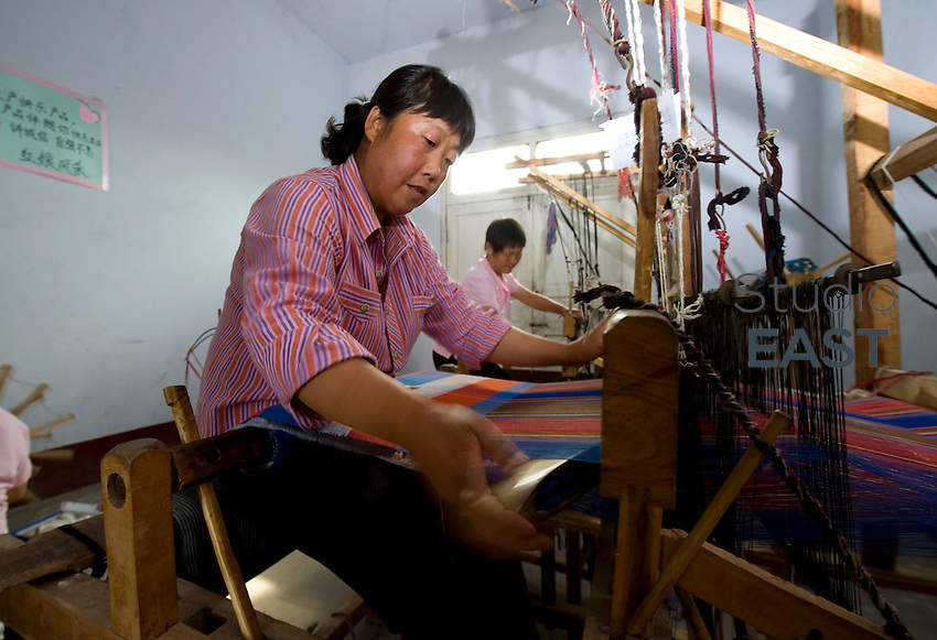 Women work, sew organic cotton, produce and sell clothes, in Fuping Development Institute worshop, near Yongji, Shanxi province, China, on June 12, 2010. Photo by Lucas Schifres/Pictobank