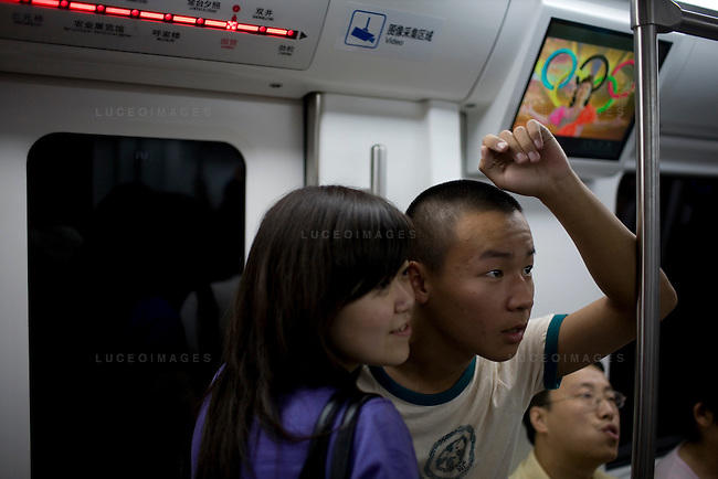 Locals watch the China vs Germany basketball game on a subway train in Beijing, China on Saturday, August 16, 2008.  Kevin German