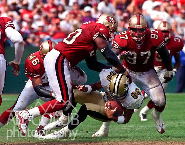 San Francisco 49ers vs. New Orleans Saints at Candlestick Park Sunday, September 14, 1997.  49ers beat Saints  33-7.  San Francisco 49ers defensive tackle Junior Bryant (90) tackles New Orleans Saints wide receiver Andre Hastings (88).