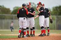 Edgewood Eagles head coach Al Brisack takes the ball from starting pitcher Joseph Kalafut (6) as Max Orput (16), Ryan Fields (9), Kyle Semrad, and catcher Jacob Popp look on during a game against the Babson Beavers on March 18, 2019 at Lee County Player Development Complex in Fort Myers, Florida.  Babson defeated Edgewood 23-7.  (Mike Janes/Four Seam Images)