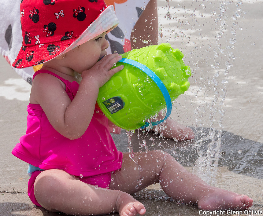 Charlie Costley, three and his younger sister Kate, nine-months-old play with cool water at the Point Edward slash pad. The kids are in Sarnia with parents Lauren and Andrew Costley, of Acton, and are in town visiting relatives.