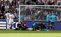 Pictured: Neil Taylor of Swansea is seen by team physios after suffering an injury from Peter Odemwingie of West Bromwich Albion (2nd R) who is shown a yellow card from match referee Martin Atkinson. Saturday 17 September 2011<br /> Re: Premiership football Swansea City FC v West Bromwich Albion at the Liberty Stadium, south Wales.