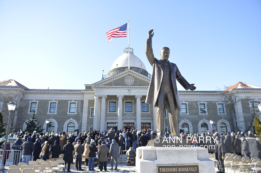 Mineola, New York, USA. January 1, 2018. Historic swearing-In of Laura Curran as Nassau County Executive, the first female County Executive, is held outdoors. Temperature was a freezing 14 ℉ Fahrenheit / -10 ℃  Celsius for the outdoor ceremony held in front of Theodore Roosevelt Executive & Legislative Building, and people in audience stood close together on and near the vast entrance stairs steps. Metal statue of President Theodore Roosevelt is in foreground.
