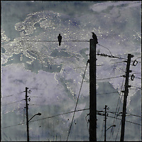 Crows on telephone lines over mixed media encaustic photo transfer of satellite image of earth at night.