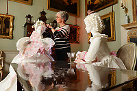 """BNPS.co.uk (01202 558833)<br /> Pic: ZacharyCulpin/BNPS<br /> <br /> Denise applies the finishing touches spectacular paper costumes. <br /> <br /> Ori-garments -  Artist Denise Watson has created a stunning 1750's masquerade Christmas Ball with characters made entirely from paper at the National Trust's Uppark House in West Sussex.<br /> <br /> Denise has dressed 14 shop mannequins with clothes, shoes, masks, fans, floral details, hair and even jewellery made from things like tissue paper, gift wrap and brown parcel paper. <br /> <br /> The festive display was inspired by Admiral Lord Gambier's memoirs in which he quotes from Lady Sarah Featherstonhaugh's journal of 1753 where she wrote: """" The whole party afterwards proceed to Uppark, where they passed a cheerful happy Christmas in the most friendly society, and enlivened their neighbourhood with some masked balls.""""<br />  <br /> The design to the finished result took a total of three months. Denise said, """"I am really delighted with the final result. It has been a joy to work at Uppark using the grand rooms and to recreate an event which actually took place""""."""