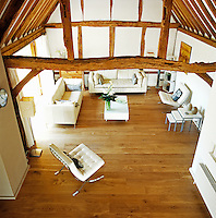 A aerial view of the double-height living room showing the exposed beamed structure of the barn's vaulted ceiling
