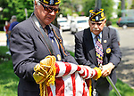 American Legion members carefully roll up flags after  the Merrick Memorial Day Parade and Ceremony on Monday, May 28, 2012, on Long Island, New York, USA. America's war heroes are honored on this National Holiday.