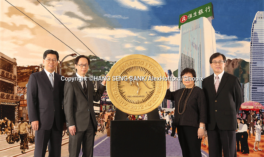 A Hang Seng Bank handout photo shows bank executives; Andrew Fung (2L), Executive Director and Head of Global Banking and Markets, Donald Lam (L), Head of Corporate and Commercial Banking, Rose Lee (R), Vice-Chairman and Chief Executive and Nixon Chan (2R), Head of Retail Banking and Wealth Management, flanking what the bank says is the world's largest gold coin, Hong Kong, China, 09 January 2014. Hang Seng Bank has been awarded the exclusive right to display the monster coin, the '2012 Australian Kangaroo One Tonne Gold Coin', in Hong Kong. Issued by The Perth Mint as legal tender with a monetary denomination of one million Australian dollars (Euro 655,704.00), the coin contains one tonne of 99.99% pure gold and is officially recognised by Guinness World Records as the largest and heaviest coin in the world. As at 8 January, the gold value of the coin is more than HKD305 million (Euro 28,911,715.00). It is the first time the coin has been available for public viewing outside Australia.