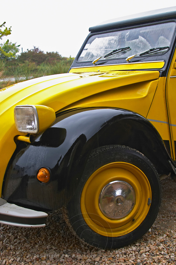 An old black and yellow Citroen 2CV 2 CV, detail of the front left side and wheel, headlight Domaine la Tourade, André Andre Richard, Gigondas, Vacqueyras, Vaucluse, Provence, France, Europe