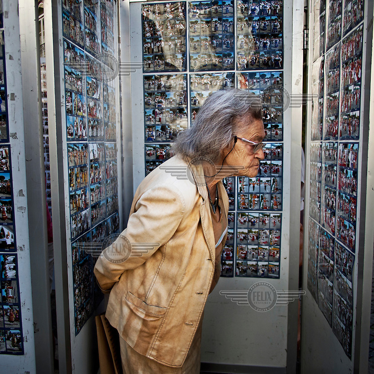 An elderly woman looks at photographs on a local photographer's contact sheets which are for sale.