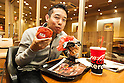A customer enjoys eating the new ''AKA SAMURAI CHICKEN'' and ''AKA SAMURAI BEEF'' burgers during the new Burger King's red burgers launching event on Friday July 3, 2015, in Tokyo, Japan. The two new burgers use red buns and red cheese, colored by tomato powder and spicy red sauce and will be sold at Japanese branches until August. The AKA SAMURAI CHICKEN costs 540 JPY (4.39 USD) and the AKA SAMURAI BEEF costs at 690 JPY (5.61 USD). As a part of the promotion Burger King plans to launch two new black burgers on August 21st. (Photo by Rodrigo Reyes Marin/AFLO)
