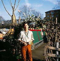 A portrait of Emma Freemantle, a fashion stylist/ artist standing by her bohemian canal boat in London