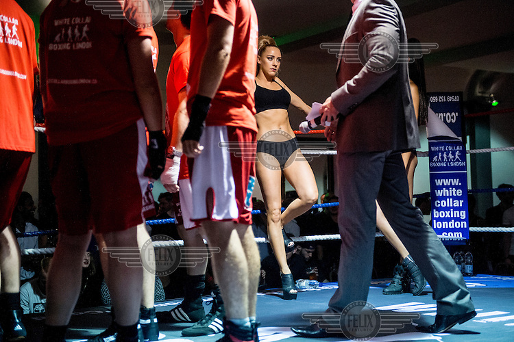 A woman in a swim suit waits in the ring during an intermission at a white collar boxing event at the London Irish Centre where the 'Carpe Diem' boxing event is taking place. <br /> <br /> 'White-collar boxing' is a growing phenomenon amongst well paid office workers and professionals and has seen particular growth in financial centres like London, Hong Kong and Shanghai. It started at a blue-collar gym in Brooklyn in 1988 with a bout between an attorney and an academic and has since spread all over the world. The sport is not regulated by any professional body in the United Kingdom and is therefore potentially dangerous, as was proven by the death of a 32-year-old white-collar boxer at an event in Nottingham in June 2014. The London Irish Centre, amongst other venues, hosts a regular bout called 'Carpe Diem'. At most bouts participants fight to win. Once boxers have completed a few bouts they can participate in 'title fights' where they compete for a replica 'belt'.