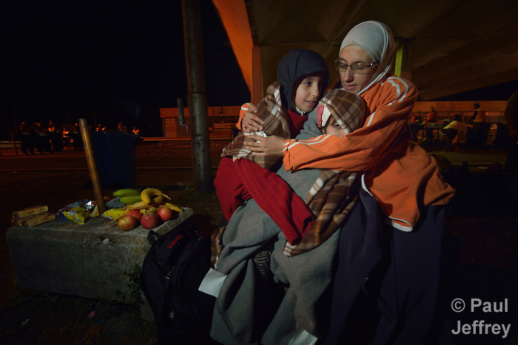 Mayada Ari was a math teacher in Deir ez-Zor, Syria, when the fighting caused her eyesight to deteriorate, and she was constantly afraid for her children. So she and her husband and their four kids set off for western Europe. &quot;We heard that the best life is in Germany,&quot; she said. They traversed Turkey and Greece and Macedonia and Serbia until arriving in Hungary. She said the journey has been difficult and dangerous. &quot;But it was more dangerous to remain at home,&quot; she said.<br /> <br /> In this image, she cuddles two of her children as they shiver in the cold night air as the family leaves the Hungarian town of Hegyeshalom and prepares to cross the border into Austria. <br /> <br /> At the border crossing, she and her family received food and blankets from Hungarian Interchurch Aid, a member of the ACT Alliance. <br /> <br /> Hundreds of thousands of refugees and migrants flowed through Hungary in 2015, on their way to western Europe from Syria, Iraq and other countries.