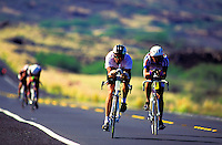 Front view of two bikers competing side by side  in the annual Ironman Triatholon on the Big Island of Hawaii.
