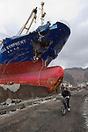 A man cycles past the Asia Symphony cargo ship which was swept ashore by the March 11 tsunami in the port of Kamaishi City, Iwate Prefecture Japan. Photographer: Robert Gilhooly  .