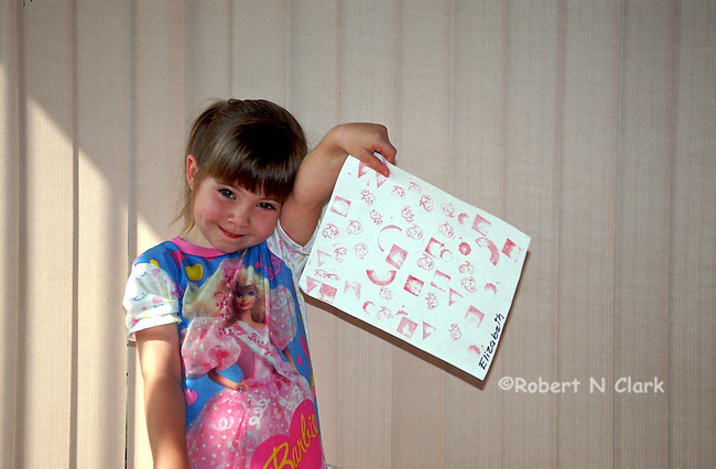 Girl showing off her preschool homework and artwork