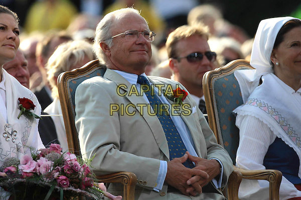 KING CARL GUSTAF & QUEEN SILVIA OF SWEDEN .At the celebration of Crown Princess Victoria of Sweden's 32nd Birthday, .Borgholm Stadium, Öland, Sweden, .14th July 2008..royal royal family royals half length red  flowers sitting blouse shirt scarf head rose button hole  husband wife blue tie glasses beige suit .CAP/PPG/WS.©Willi Schneider/People Picture/Capital Pictures