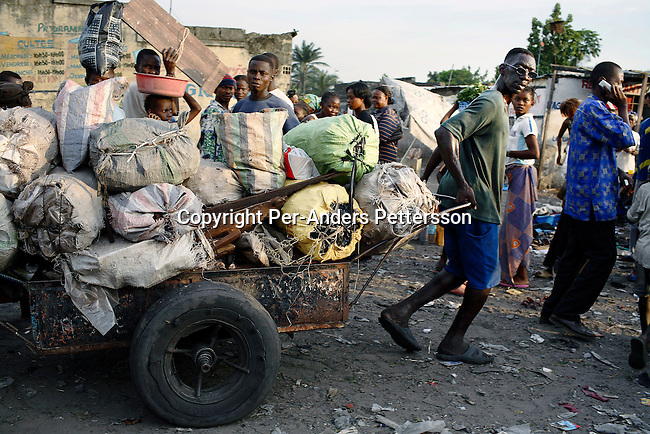 KINSHASA, DEMOCRATIC REPUBLIC OF CONGO FEBRUARY 28: An unidentified man pushes a cart with charcoal on a muddy road leading the central market on February 28, 2006 in central Kinshasa, Congo, DRC. The area, one of the poorest in the capital, is littered with garbage and the roads are in very bad condition. Kinshasa, a city of about eight million people is battling with bad infrastructure and no public transport. Congo, DRC is in ruins after forty years of mismanagement by the corrupt dictator and former president Mobuto Sese Seko. He fled the country in 1997 and a civil war started. The country is planning to hold general elections by July 2006, the first democratic elections in forty years.(Photo by Per-Anders Pettersson)