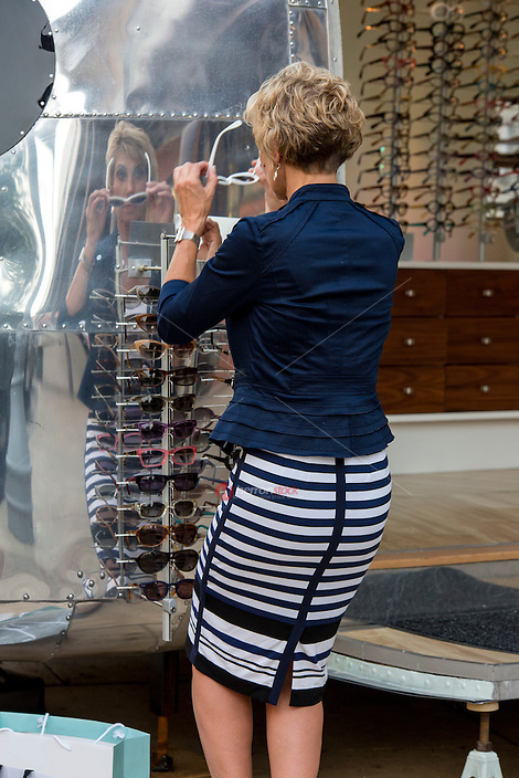 Attractive female shopper tries on new sunglasses at an Austin outdoor shopping mall