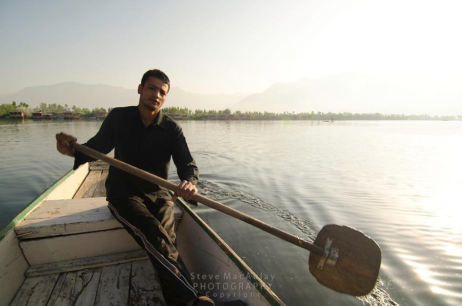 Young Kashmiri man paddling a traditional shakira, Dal Lake, Srinagar, Kashmir, India.