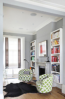 Colour co-ordinated bookcases create bands of colour against the grey walls of this sitting room