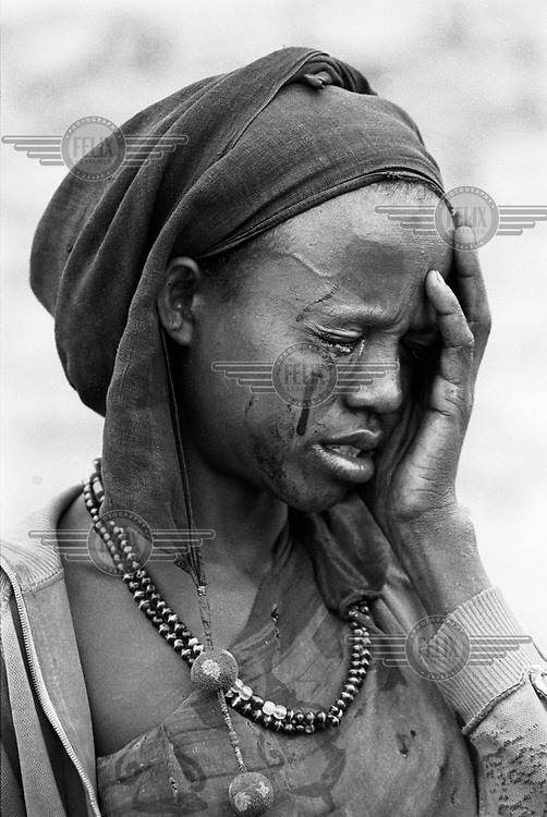 © Paul Lowe / Panos Pictures..Baidoa, SOMALIA  1992.A woman cries after being beaten by an armed gang  during the 1992 famine caused by the civil war in somalia..In 1991 President Barre was overthrown by opposing clans,  but they failed to agree on a replacement and plunged the country into lawlessness and clan warfare. In December 1992 US Marines landed  near Mogadishu ahead of a UN peacekeeping force sent to restore order and safeguard relief supplies.  The US forces withdrew in 1993 following the debacle of Black Hawk Down..CROPPED OR DIGITALLY MODIFIED IN ANY MEDIUM AND ITS CAPTION MAY NOT BE ALTERED WITHOUT THE PRIOR WRITTEN AUTHORISATION OF THE PHOTOGRAPHER OR HIS AGENT...