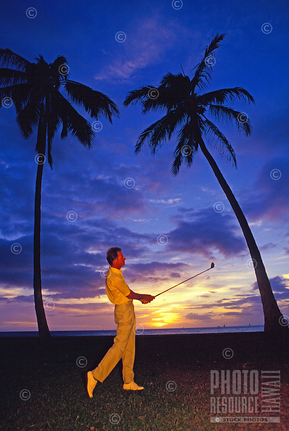 Golfer at sunset with palm trees