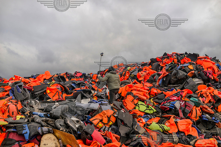 A virtual reality film maker climbs a pile of abandoned life jackets that have built up on an area of waste ground.