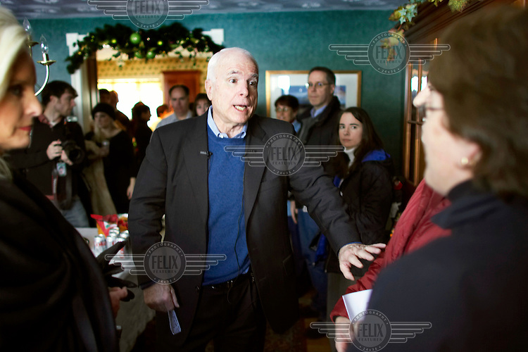 John McCain, Republican candidate for President, greets people as he arrives at a house party during the New Hampshire primary campaign.