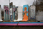 Decorated sections of the former Berlin Wall standing in a pen beside the river Spree. The route of the Wall, which stood from 1961-1989, has been developed into the 'Mauerweg,' a thoroughfare which traces most of the route of the Wall which encircled the city and divided it into East and West Berlin during the Cold War. In the years following the 1989 civil uprising in the German Democratic.Republic, most of the Wall was removed as part of the reunification strategy which united the pro-Soviet DDR and the Federal Republic of (West) Germany.