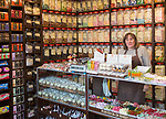 Interior with shop assistant and jars of traditional sweets,  Olde Sweet Shop, Ipswich, Suffolk, England, UK