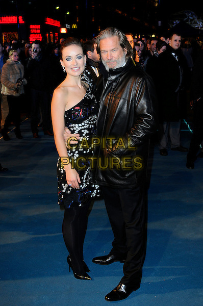 "OLIVIA WILDE & JEFF BRIDGES .At the ""Tron: Legacy"" UK Film Premiere, Empire cinema, Leicester Square, London, England, UK, .December 5th 2010..full length one shoulder black white print sleeve dress red blue leather coat jacket white shirt tights trousers shoes arm around .CAP/CAS.©Bob Cass/Capital Pictures."
