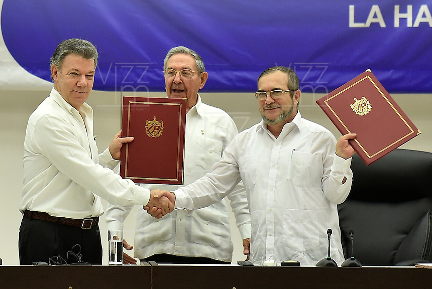 "LA HABANA - CUBA, 23-06-2016 Juan Manuel Santos, presidente de Colombia, y Rodrigo Londoño ""Timochenko"", jefe de las Farc, se dan la mano hoy en La Habana durante la firma del acuerdo para el cese al fuego y de hostilidades bilateral y definitivo entre el gobierno de Colombia y la guerrilla de las Farc. El presidente de Cuba Raul Castro fue testigo como representartnte del país garante de los acuerdos.. / Juan Manuel Santos, president of Colombia, and Rodrigo Londoño ""Timochenko"", leader of Farc at La Habana, Cuba, during the signing of the agreement of the definitive ceasefire and hostilities between Colombia Government and left guerrillas of Farc. Raul Castro, president of Cuba was the witness as representantive Country of the process. Photo: VizzorImage /  Nelson Cardenas - SIG / HANDOUT PICTURE; MANDATORY EDITORIAL USE ONLY/ NO MARKETING, NO SALES"