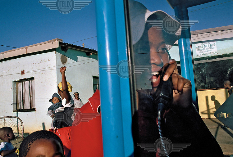 A child talks on a village pay phone as other children stand about in Springfontein.