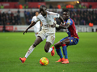 (L-R) Modou Barrow of Swansea is held back by Pape Souare of Crystal Palace during the Barclays Premier League match between Swansea City and Crystal Palace at the Liberty Stadium, Swansea on February 06 2016