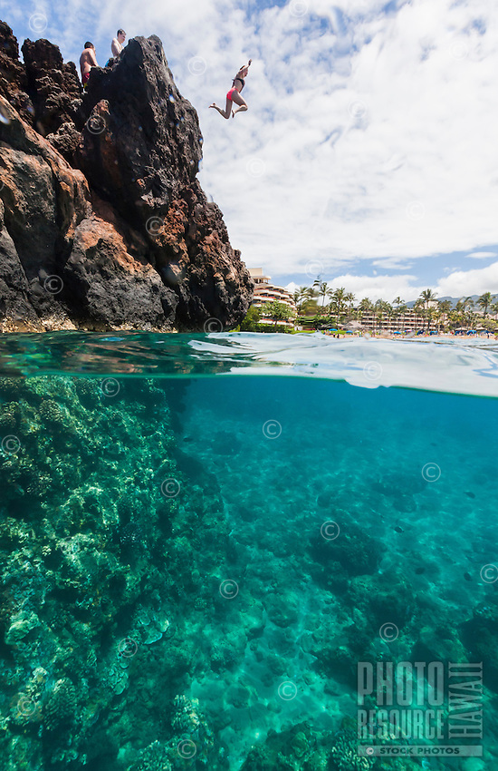 Split-level view of a girl cliff jumping into the ocean below with a view of hotels in the background on Maui.