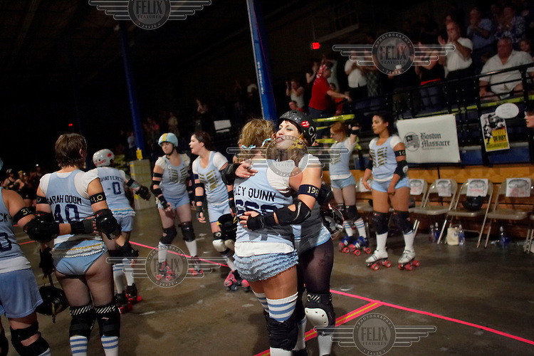 Harley Quinn hugs Claire D. Way after winning their roller derby bout in Wilmington, Massachusetts. Roller derby is an American contact sport, popular with young women, which combines both athleticism and a satirical punk third-wave feminism aesthetic.
