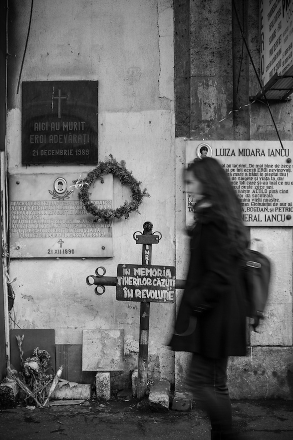A woman passes markers where protesters were killed 24 years earlier during the the Romanian Revolution in Bucharest.