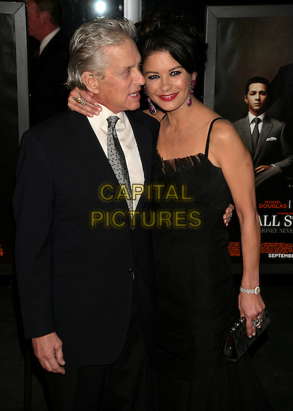 MICHAEL DOUGLAS & CATHERINE ZETA JONES.Premiere of 'Wall Street: Money Never Sleeps' at the Ziegfeld Theatre, New York City, New York, NY, USA..September 20th, 2010.half length white shirt black grey gray suit jacket tie dress married husband wife arm over shoulder mouth open profile clutch bag .CAP/LNC.©TOM/LNC/Capital Pictures.