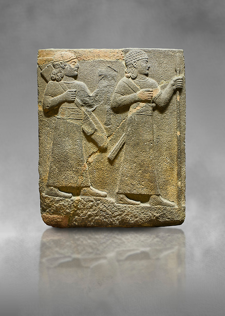 Hittite relief sculpted orthostat stone panel of Royal Buttress. Basalt, Karkamıs, (Kargamıs), Carchemish (Karkemish), 900-700 B C. Warriors. Anatolian Civilisations Museum, Ankara, Turkey.<br /> <br /> Two figures are seen, each with a long dress, a thick belt and curled hair. The figure in front carries a spear in his left hand and a long sword at his waist, and the figure behind carries an axe in his left hand and a quiver on his back.   <br /> <br /> Against a grey art background.