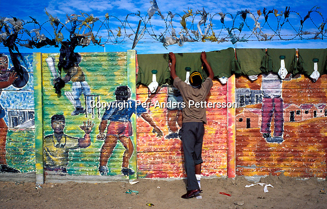 dienvpo00072 .An unidentified man hanging rugby shirts that have been laundered on a colorful wall with graffiti on July 5, 2001 in Site C Khayelitsha, a township about 35 kilometers outside Cape Town, South Africa. The township has about one million people living there. Khayelitsha is one of the poorest and fastest growing townships in South Africa. People usually come from the rural areas in Eastern Cape province to find work as maids and laborers. Most people don't find work and the unemployment rate is very high, together with lot of violence and a growing HIV-Aids epidemic itÕs a harsh area to live in..©Per-Anders Pettersson/iAfrika Photos.
