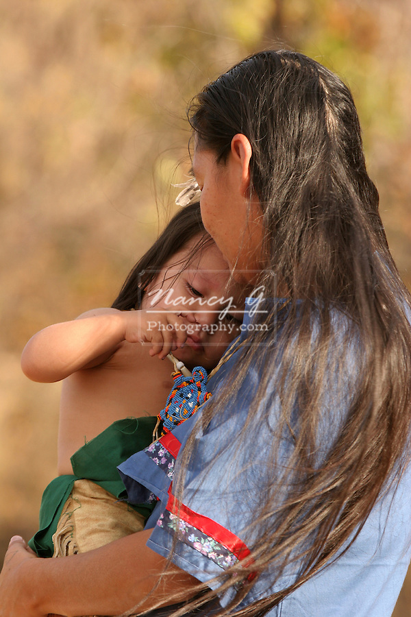 A Native American Indian mother holding and comforting her baby boy