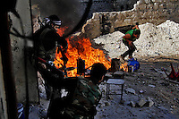 A Free Syria Army soldier runs through the line of fire after throwing a home-made grenade during a battle with loyalist soldiers in the Al-Amarya district of Aleppo on November 13, 2012. Government forces attempted to break the line early in the morning and were met with heavy resistance throughout the day. The Assad soldiers attempted to repel the resistance through mortars and grenade launchers but the rebels held the line (at least until this reporter left at sunset). ..©Javier Manzano