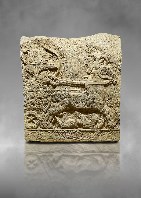 Hittite relief sculpted orthostat stone panel of Long Wall Basalt, Karkamıs, (Kargamıs), Carchemish (Karkemish), 900 - 700 BC. Anatolian Civilizations Museum, Ankara, Turkey.<br /> <br /> Chariot. One of the two figures in the chariot holds the horse's headstall while the other throws arrows. There is a naked enemy with an arrow in his hip lying face down under the horse's feet. It is thought that this figure is depicted smaller than the other figures since it is an enemy soldier. The tower part of the orthostat is decorated with braiding motifs.<br /> <br /> On a grey art background.