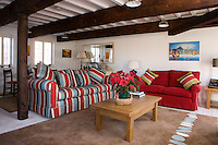 In the living room the white-painted struts of the massive beamed ceiling are echoed in the choice of a cheerful striped fabric for the large sofa situated directly below