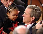 United States President George W. Bush gets a hug from Jessica Jackson, daughter of United States Representative Jesse Jackson, Jr.  (Democrat of Illinois), as he makes his way into the United States House of Representatives Chamber of the United States Capitol in Washington, D.C. for his State of the Union address January 20, 2004. Jackson's daughter fell asleep before the speech ended. <br /> Credit: Ron Sachs / CNP