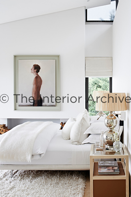 This contemporary house is an exercise in purity and harmony, where restraint and bleached colour allow simplicity and custom-made comfort to come to the fore as a luxury. The floating bed in the master bedroom is upholstered in white wool and is an Italian sun lounger design. A painting of a figure by Kerry Evans hangs above the fireplace.