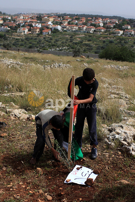 Palestinian demonstrators plant an olive tree during a protest against Israel's separation barrier in the village of Nilin, near the West Bank city of Ramallah, Saturday, April 3, 2010. Photo by Issam Rimawi