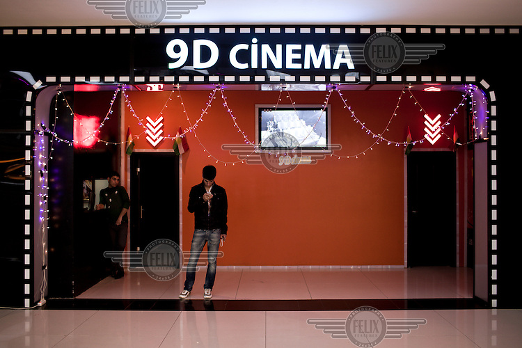 Young men stand in front a cinema inside the Family Mall in Erbil. The mall is built and owned by Turkish investors and is one of several new malls built in the region in recent years.